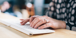 Woman's hands typing on white keyboard